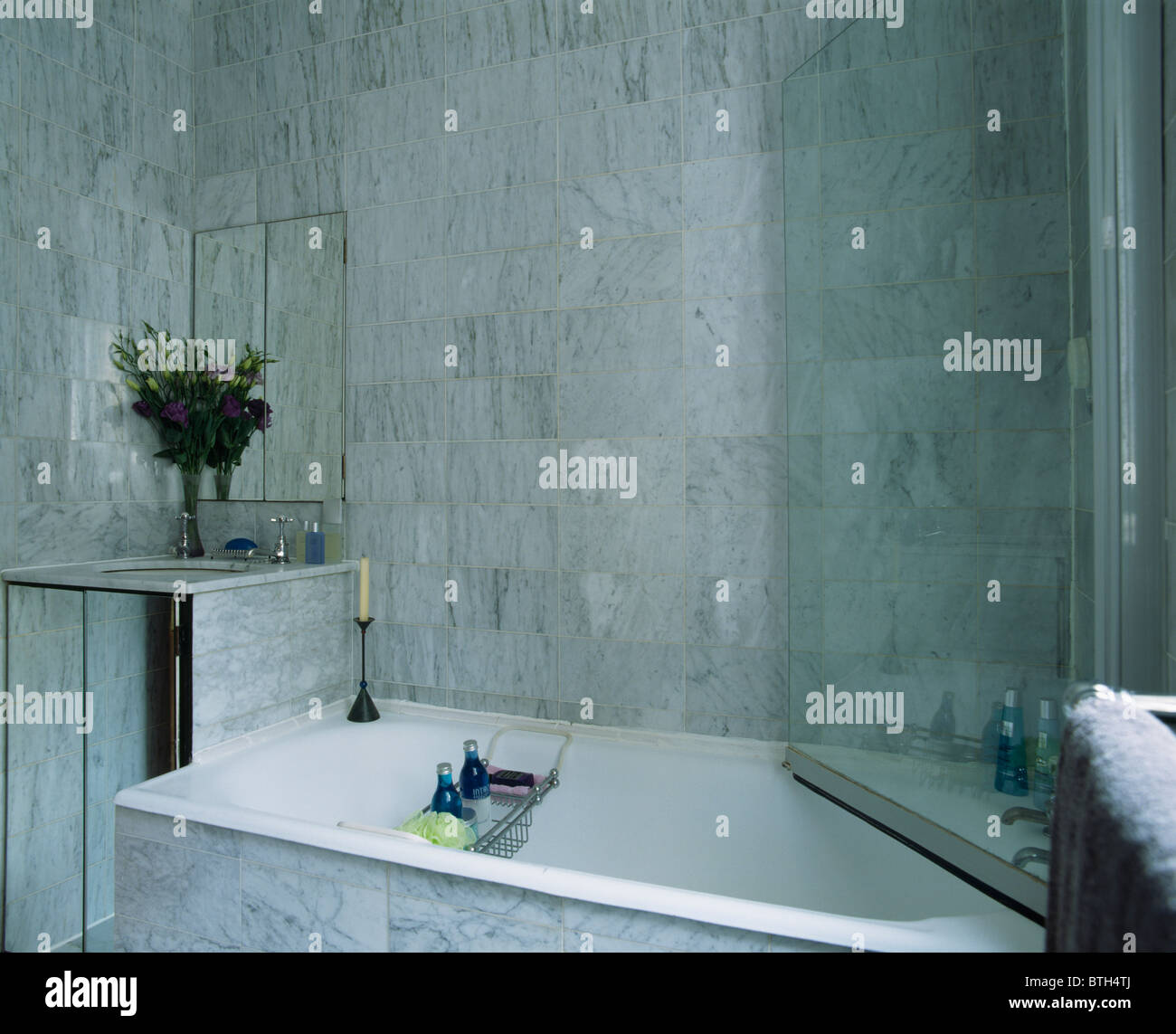 Glass shower door on bath in modern marble tiled bathroom Stock ...