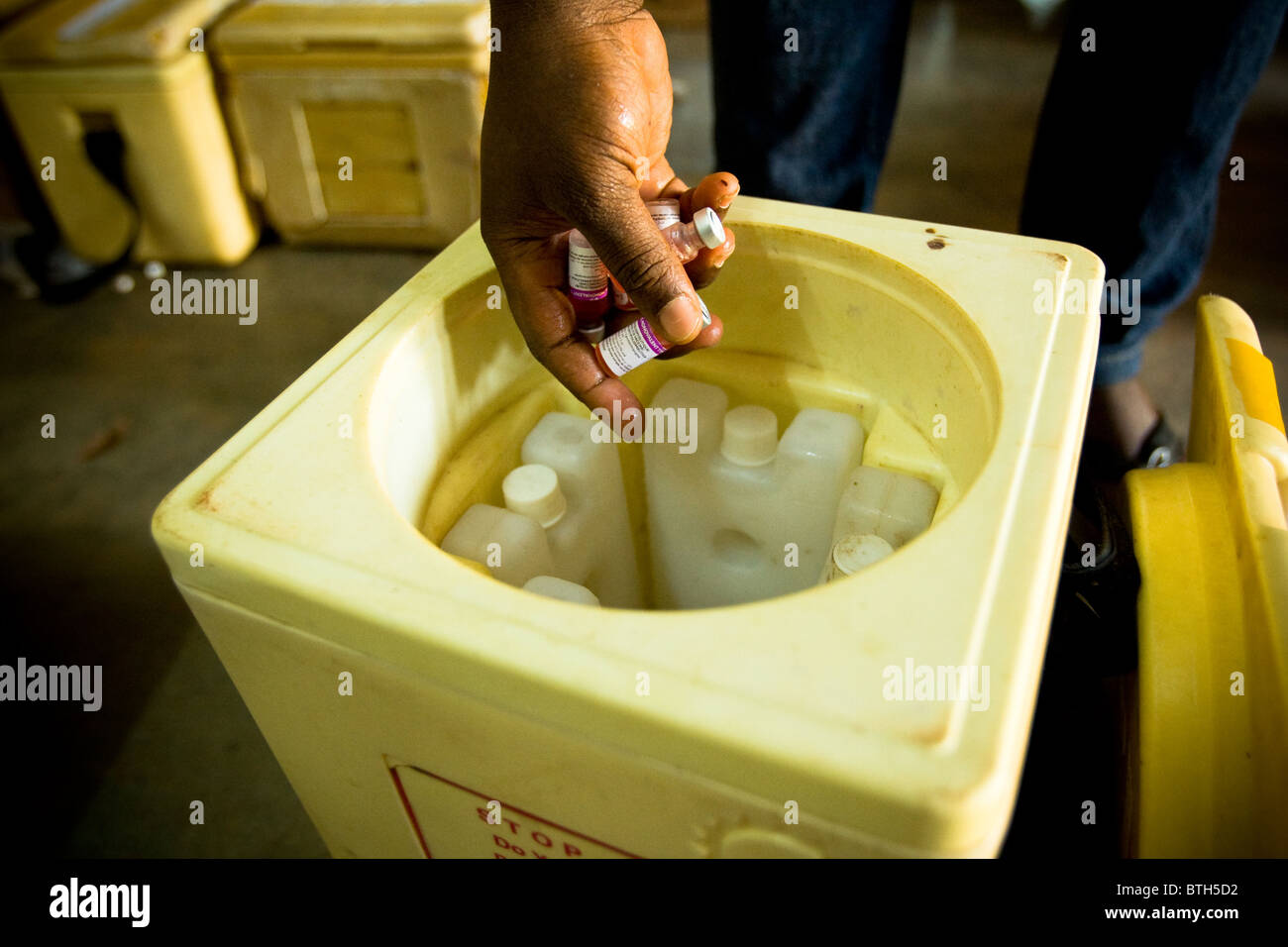 A health worker fills ice boxes with polio vaccines at the beginning of a second day of vaccination - Stock Image