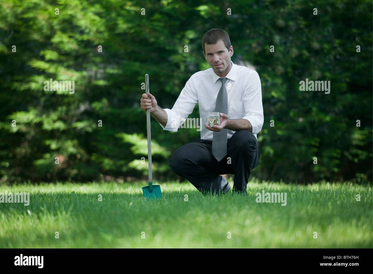 Businessman on lawn with shovel and jar of coins - Stock Image