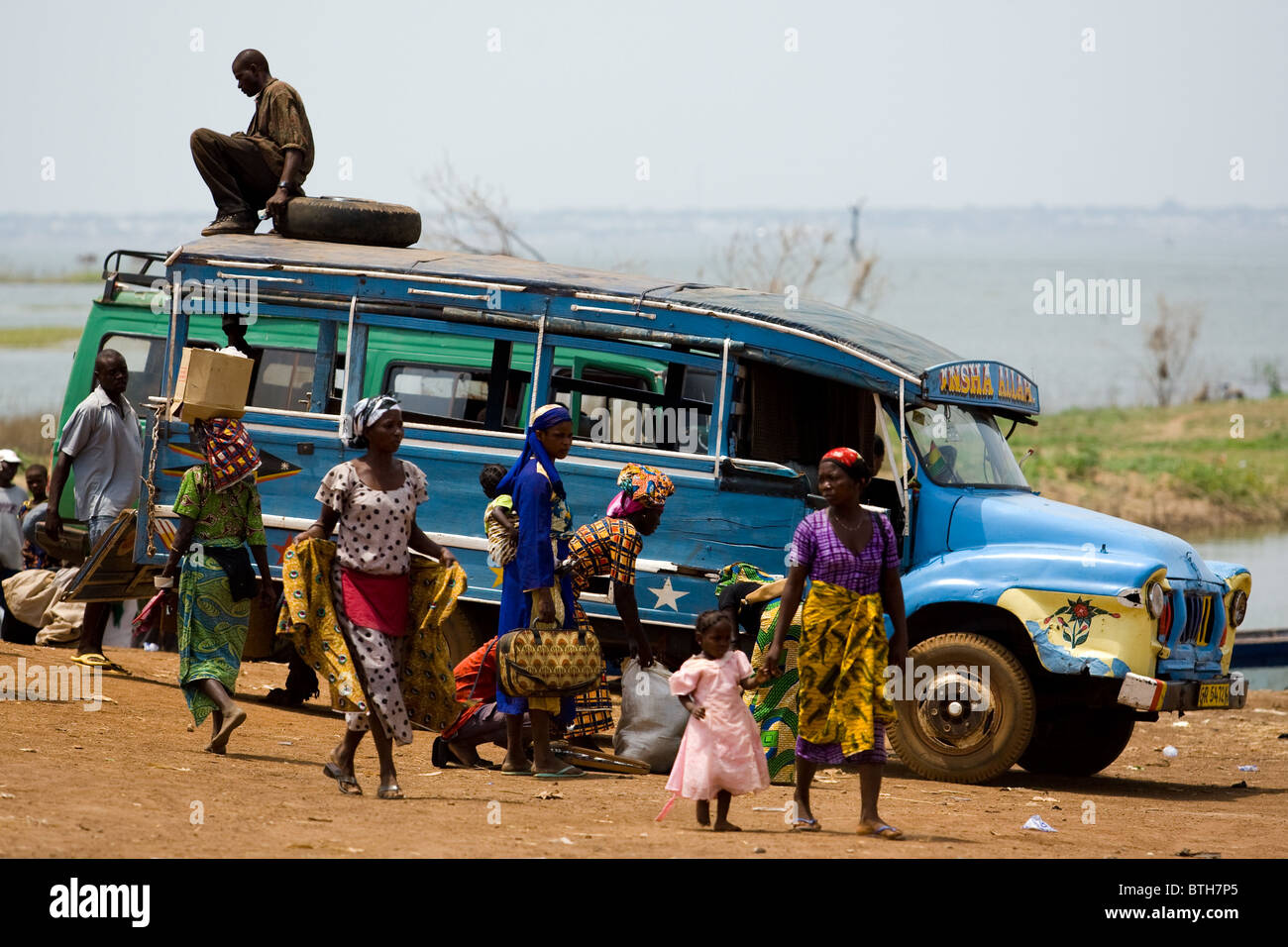Local transportation awaits passengers at a ferry terminal on the shore of Lake Volta in Makango, northern Ghana - Stock Image
