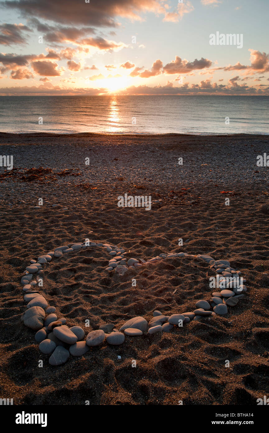 A heart shape made from stone stones rocks pebbles at sunset on Aberystwyth beach wales UK - Stock Image