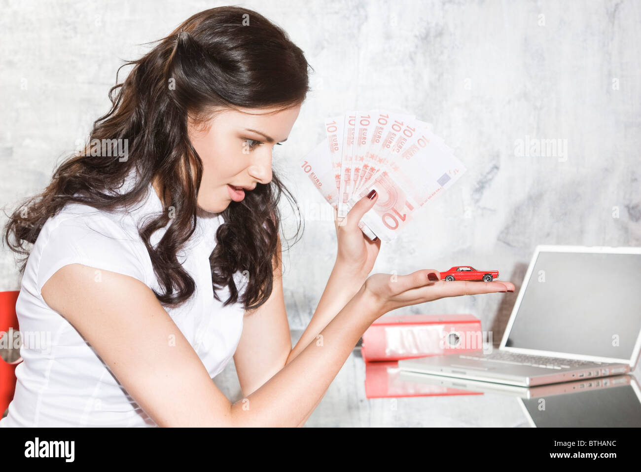 young woman saving money for a car - Stock Image