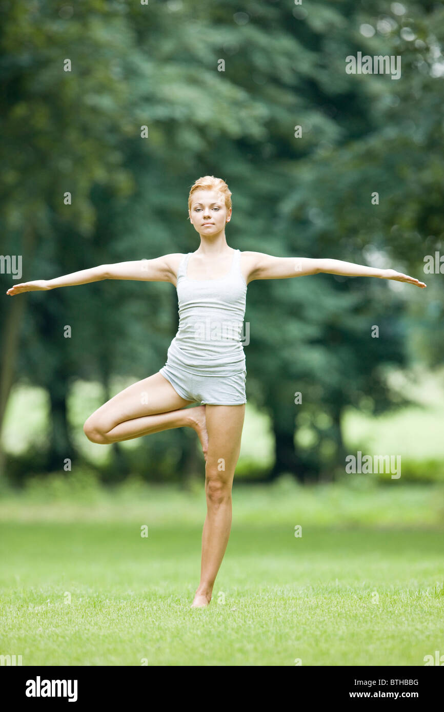 woman doing yoga in park Stock Photo