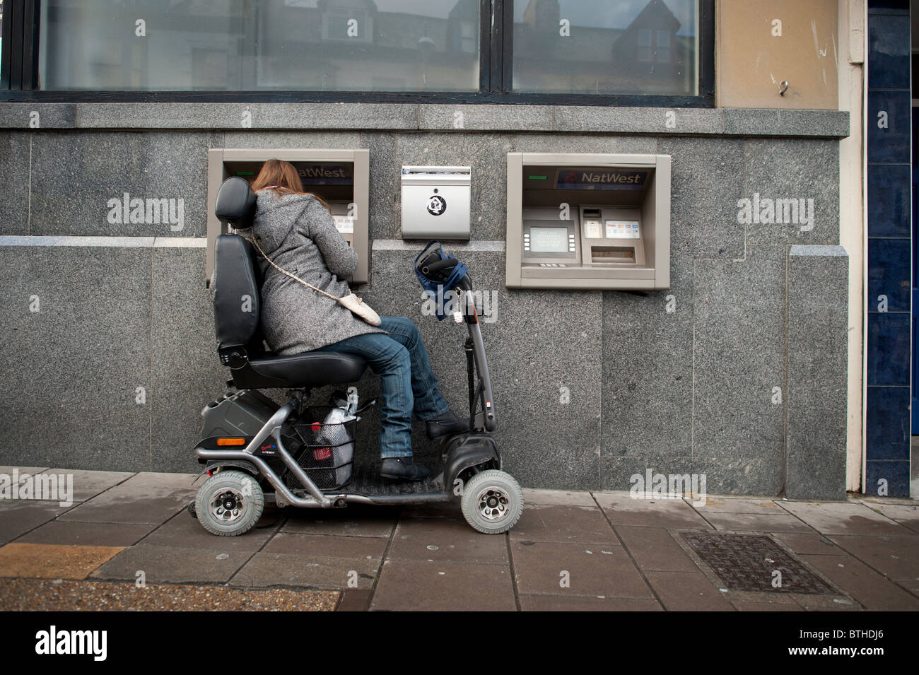 a woman in a powered wheelchair scooter using an ATM cash machine, UK - Stock Image