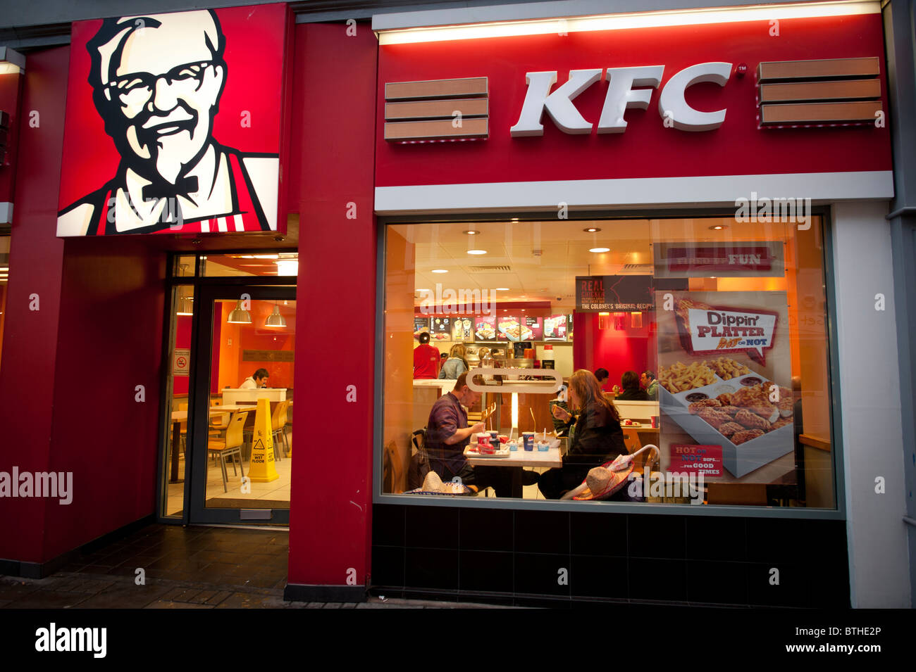 Exterior, night, people eating in a branch of KFC, kentucky fried chicken, fast food restaurant, UK - Stock Image