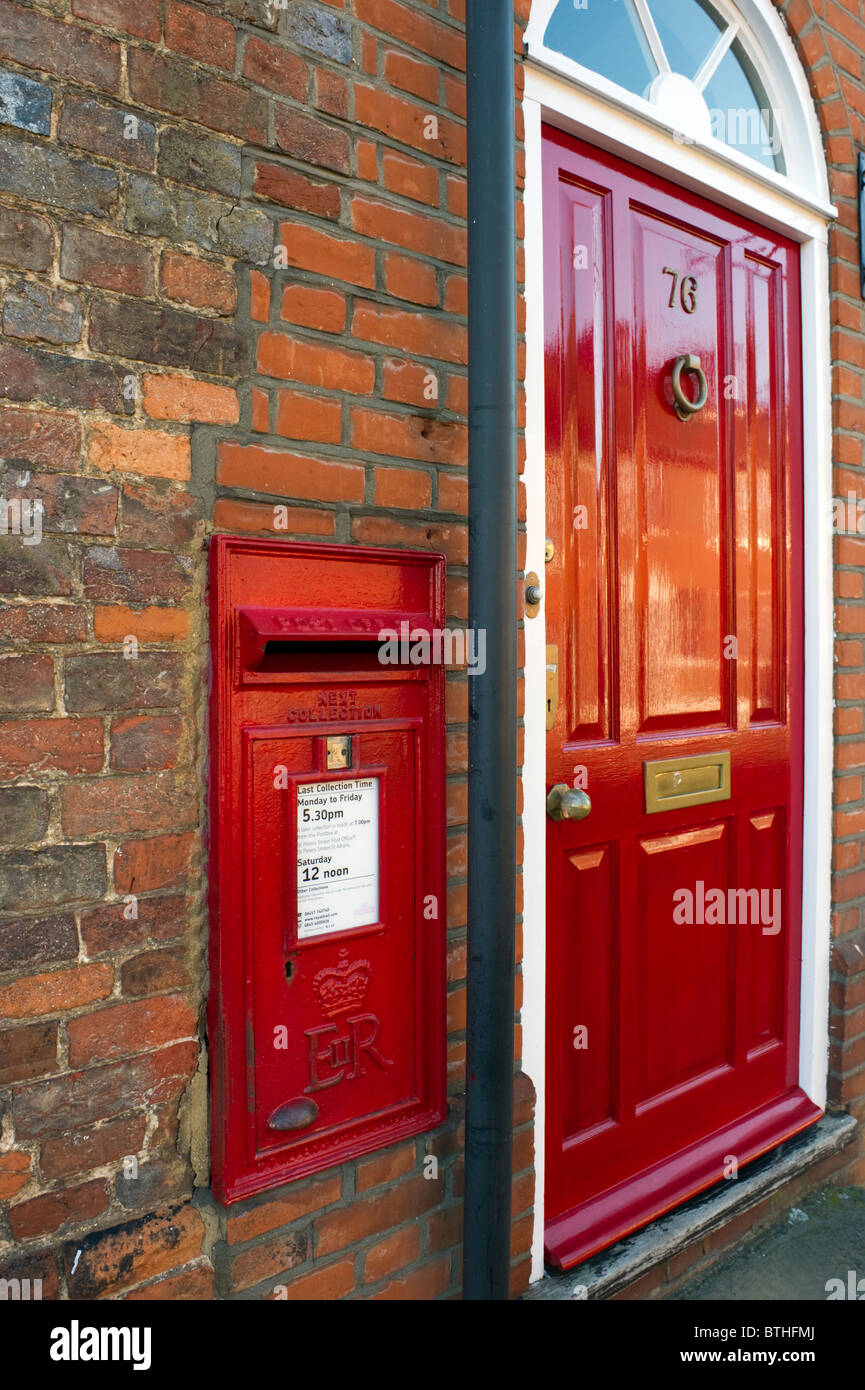 Red Letter Post Box In A Brick Wall Next To A Red Front Door In