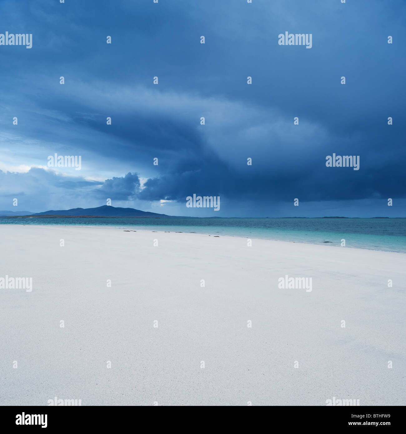 Scenic white sand beach with stormclouds overlooking Sound of Harris, Berneray, Outer Hebrides, Scotland - Stock Image