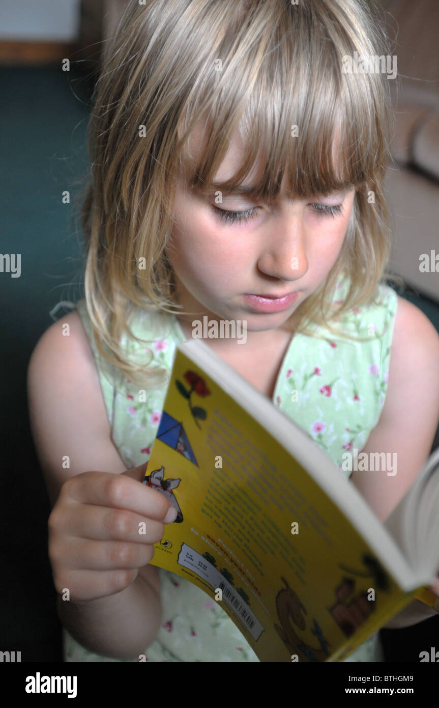 An 8 year old girl reading in her living room. - Stock Image