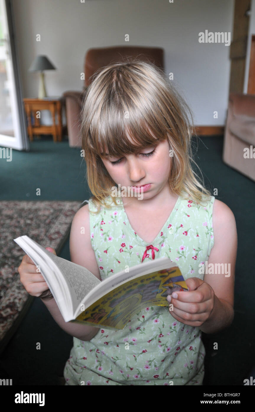 An 8 year old girl reading in her living room - Stock Image