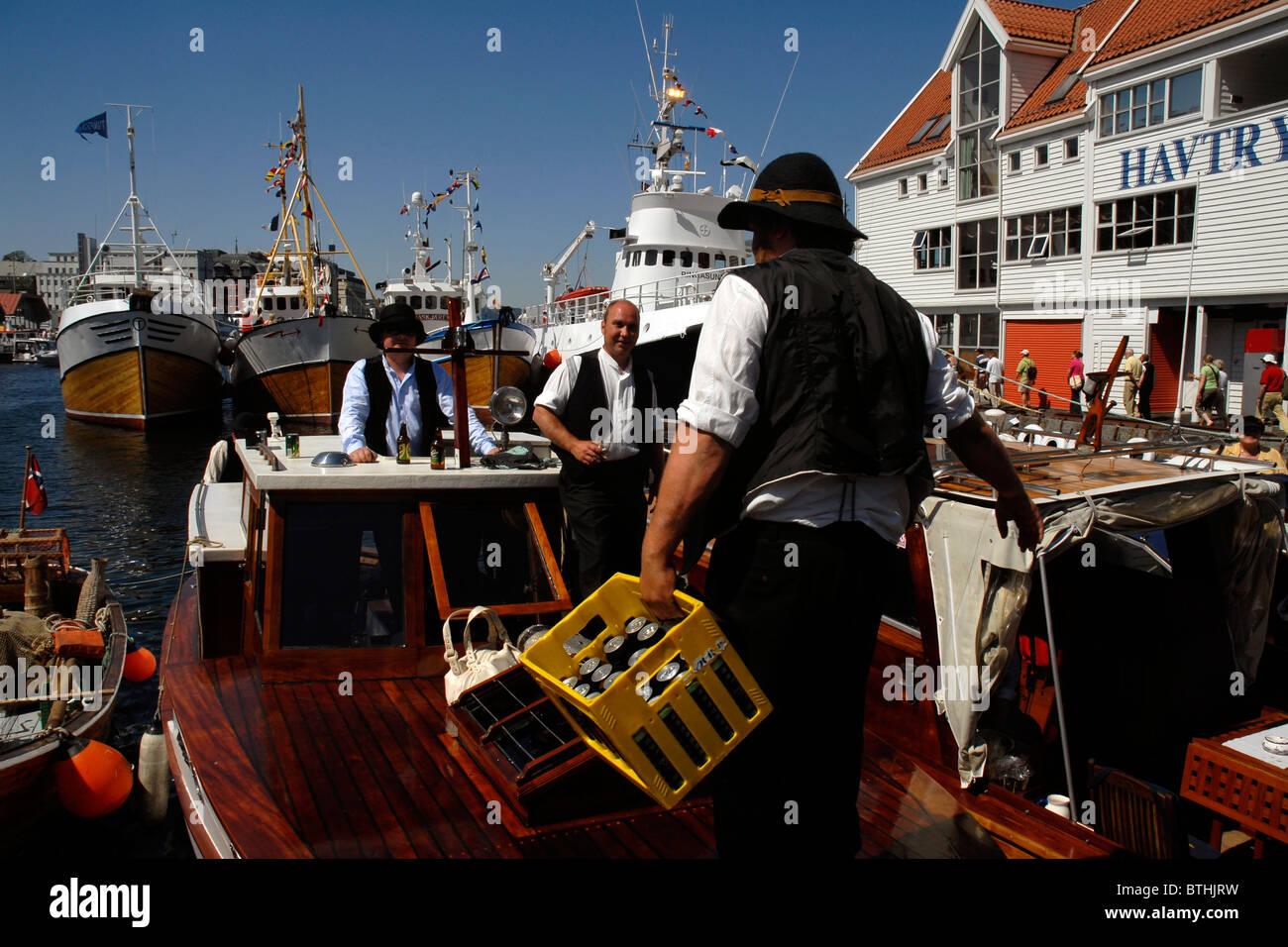 Men drinking beer at The Farmer Day Celebration, Vagen, Old Harbour, Bergen, Norway. - Stock Image