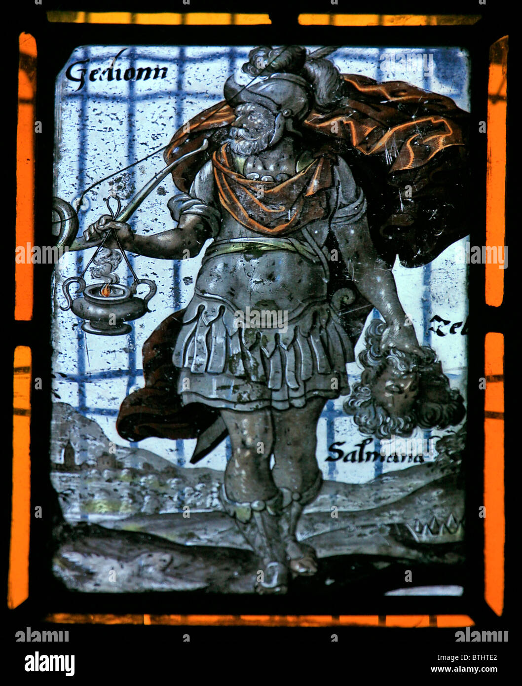 A Stained glass window depicting Gideon with trumpet and clay bottle and torch, Flemish School, circa 17th century Stock Photo