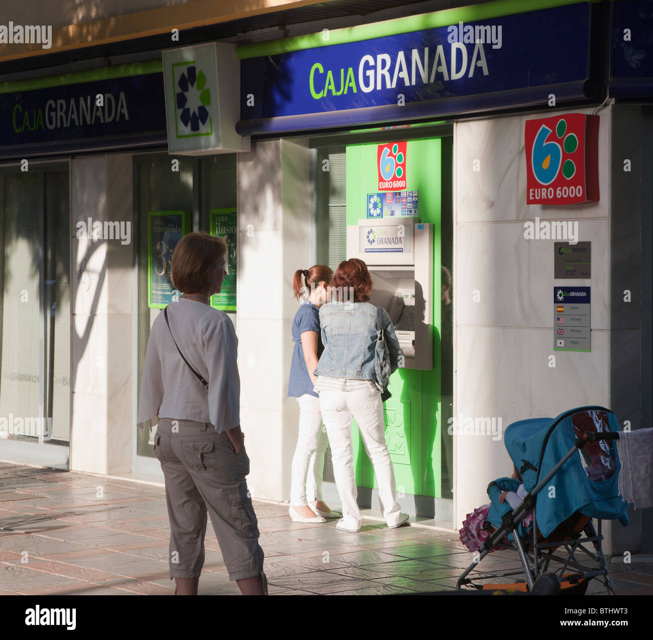 Clients taking money from cash point outside Caja Granada branch in Fuengirola, Malaga Province, Costa del Sol, - Stock Image