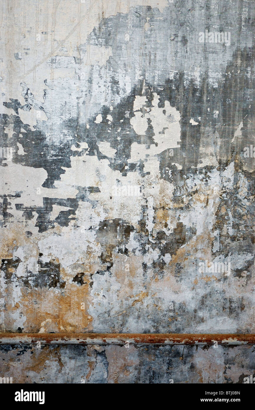 Old grungy wall texture. Peeling stained surface background. - Stock Image