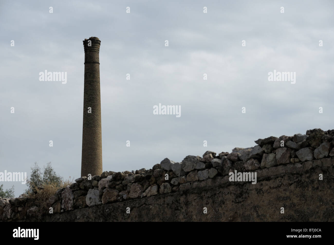 Stone wall and brick chimney of an old factory. Industrial architecture. - Stock Image