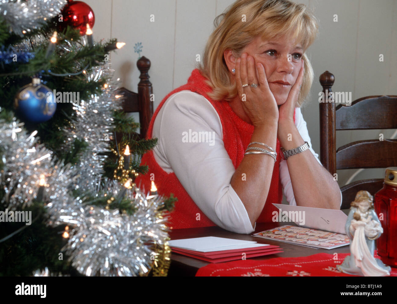 Christmas blues: Adult woman contemplating near christmas tree an christmas carts, she is unhappy. - Stock Image