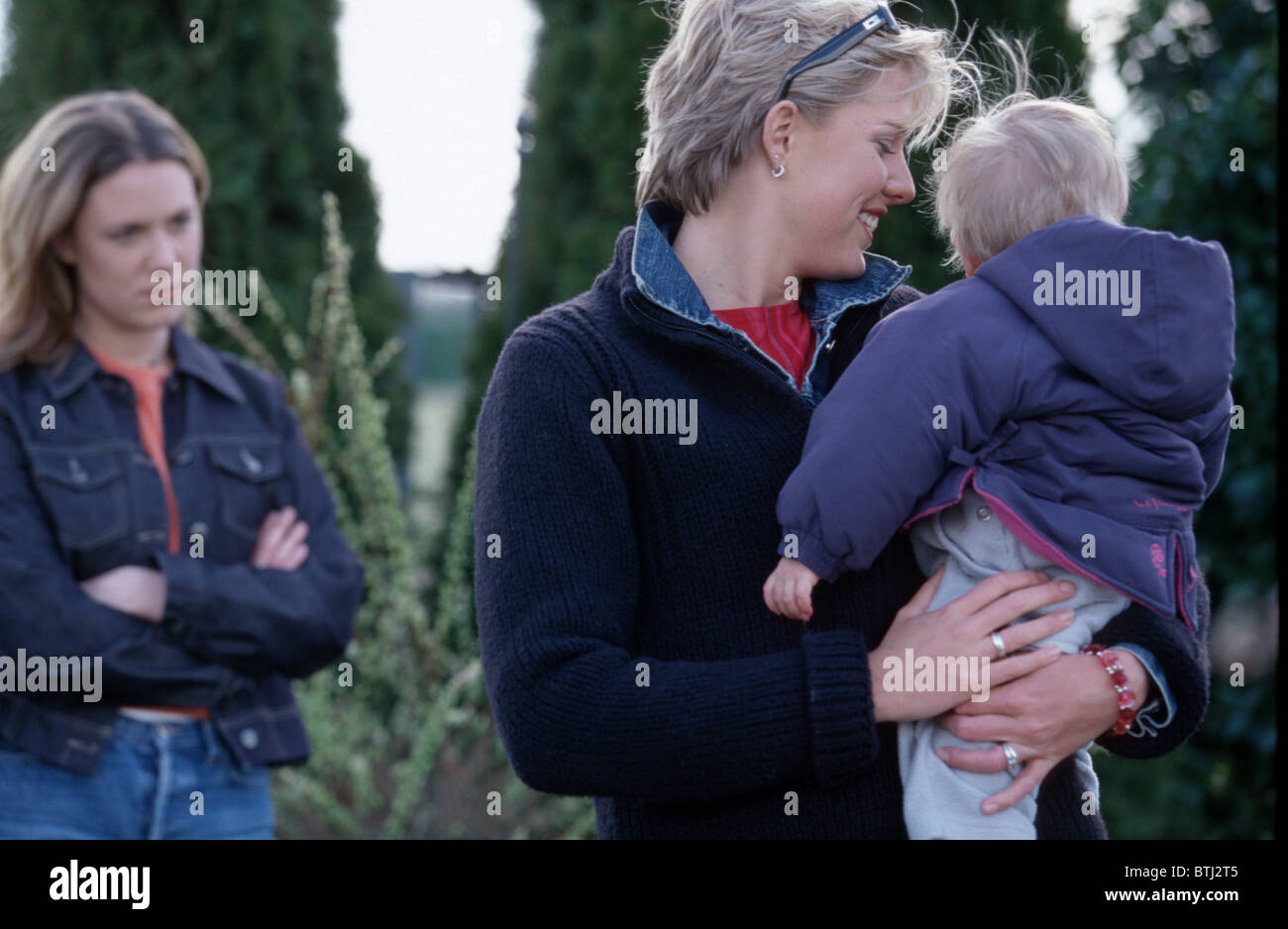 Two women one child three people - Stock Image