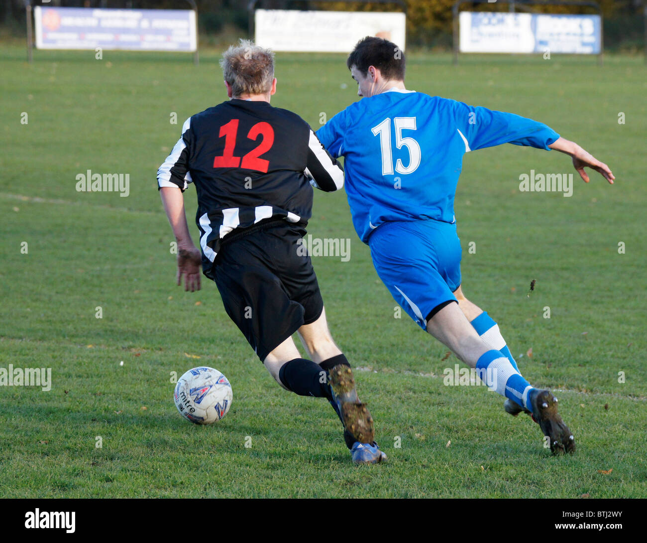Kelso, Scotland - rival players in amateur weekend league football clash in a tackle for possesion of the ball - Stock Image