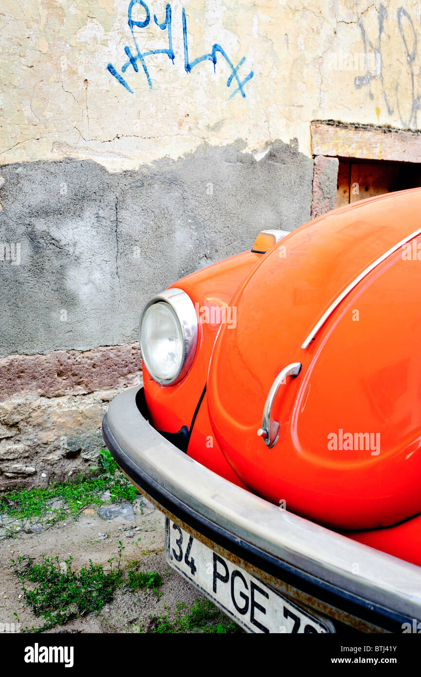 A bright orange volkswagen beetle in the streets of Cunda Island, Turkey. - Stock Image