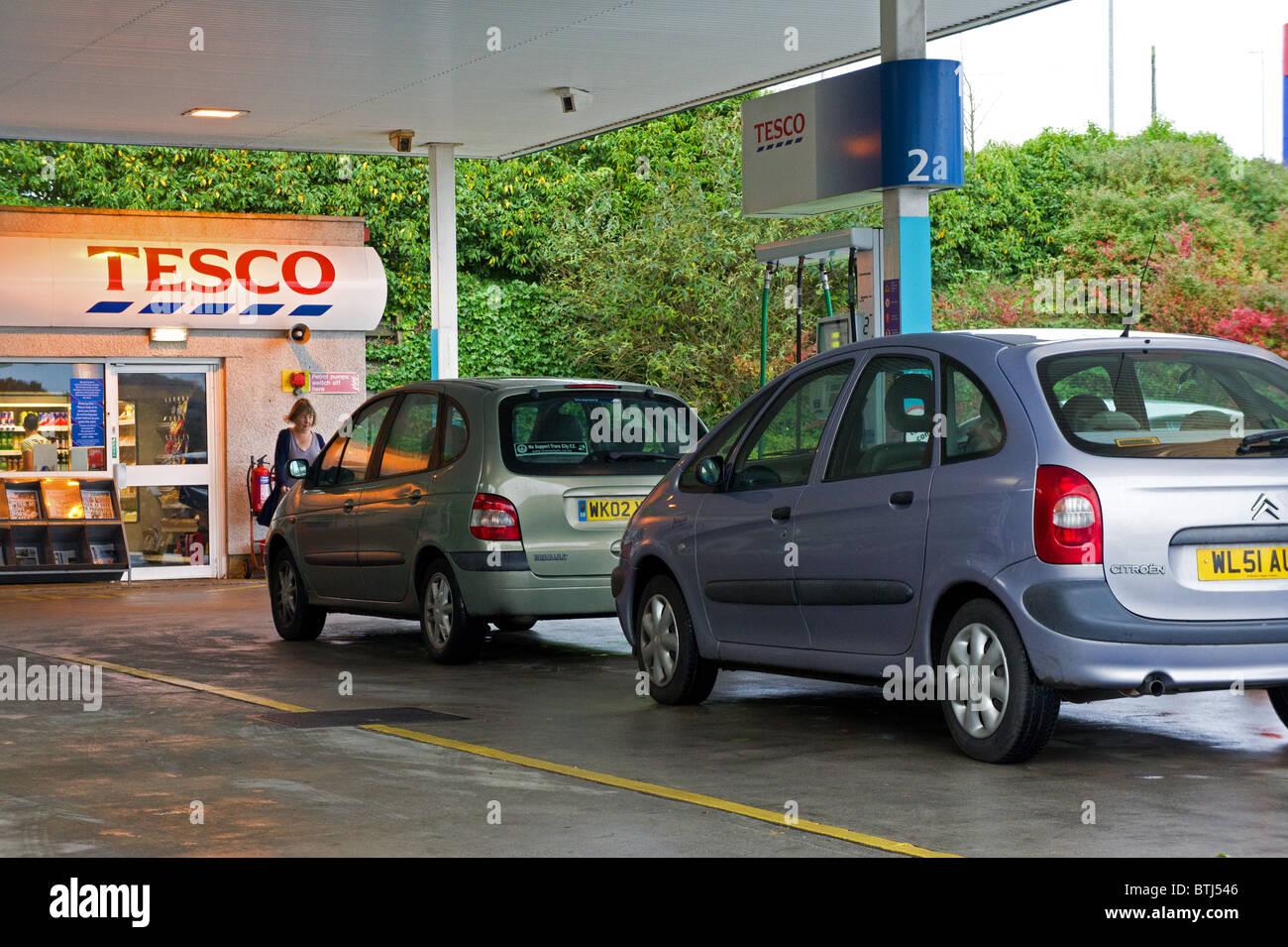 cars waiting for fuel at a Tesco petrol station, uk - Stock Image