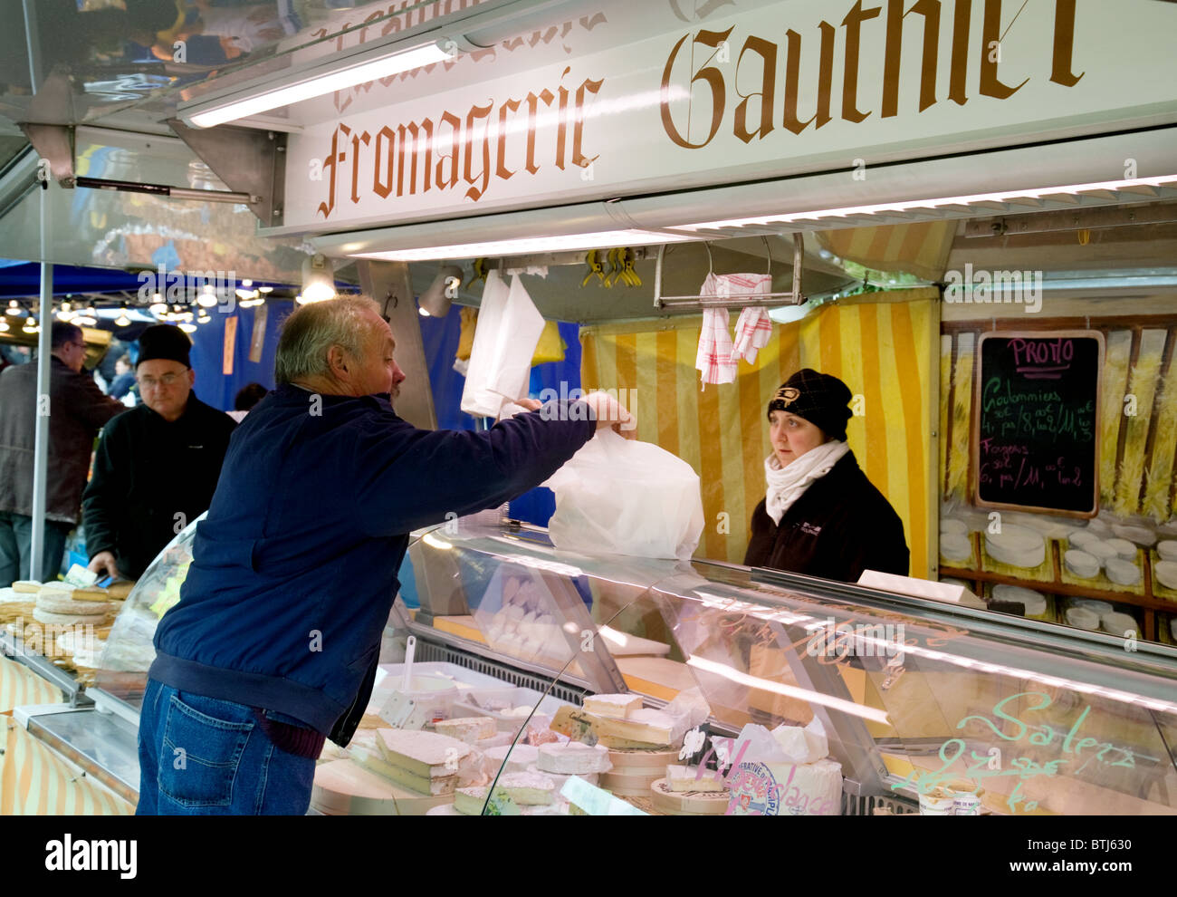 shopping for cheese at a Fromagerie (Cheese stall), Coulommiers town street market near Paris,  ile de france France - Stock Image