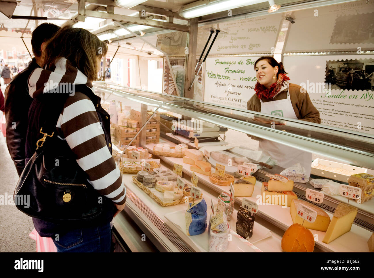 Women shopping for cheese at a fromagerie (Cheese stall), Coulommiers town street market near Paris,  ile de france - Stock Image