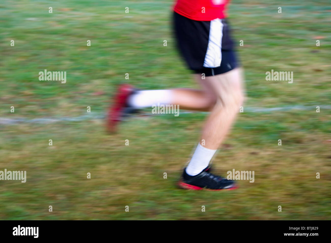 Motion blur of a runner in a cross country race - Stock Image