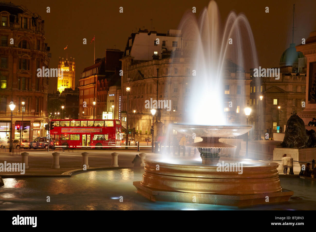 Fountain and bus, Trafalgar Square, and Houses of Parliament, London, England, United Kingdom - Stock Image