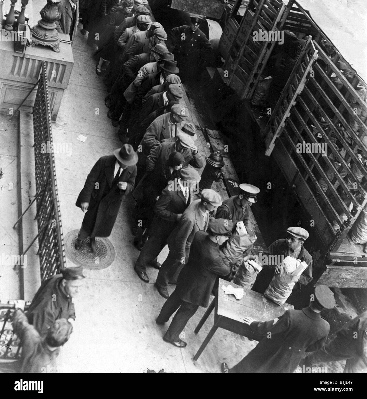 Food handouts in New York in 1930. Police stations were used as distribution centers. Photo shows food being distributed - Stock Image
