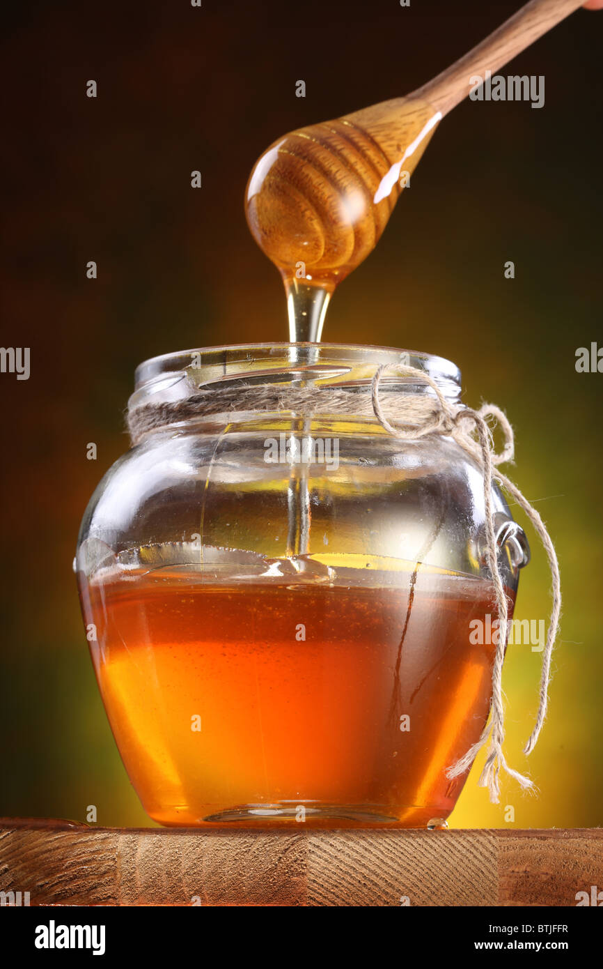 Sweet honey pouring from drizzler into the pot. Pot is on wooden table. - Stock Image