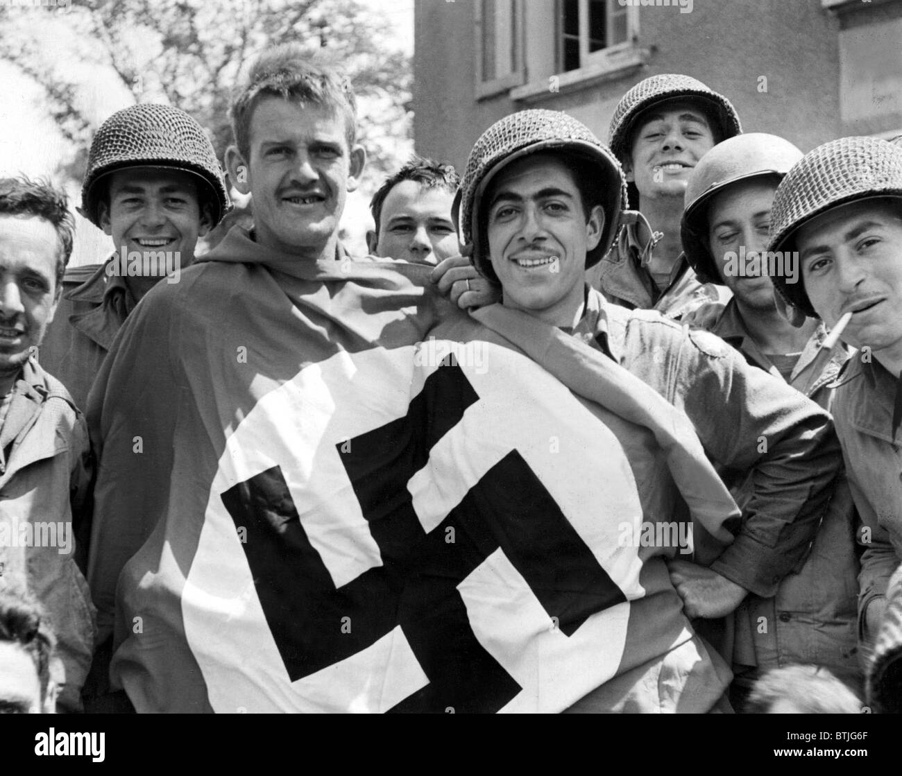 CHERBOURG, FRANCE-- A comandeered Nazi flag held by American soldiers after the liberation of Cherbourg, July 1, Stock Photo