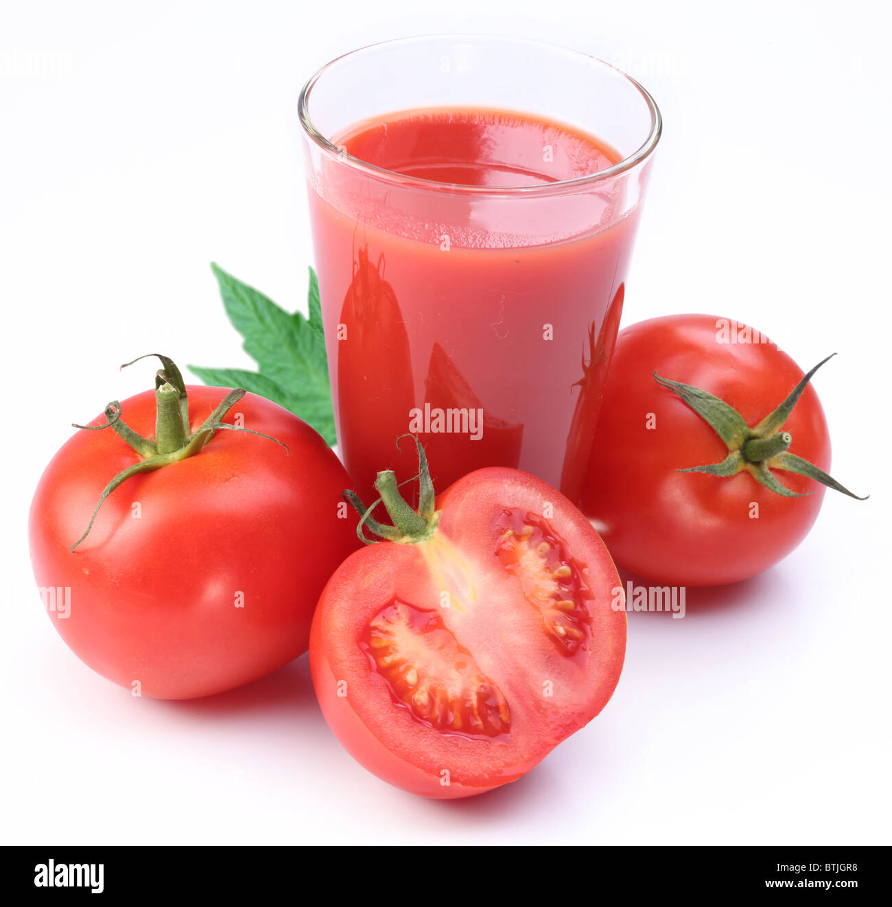 Full glass of fresh tomato juice and tomatoes are round the galss. - Stock Image