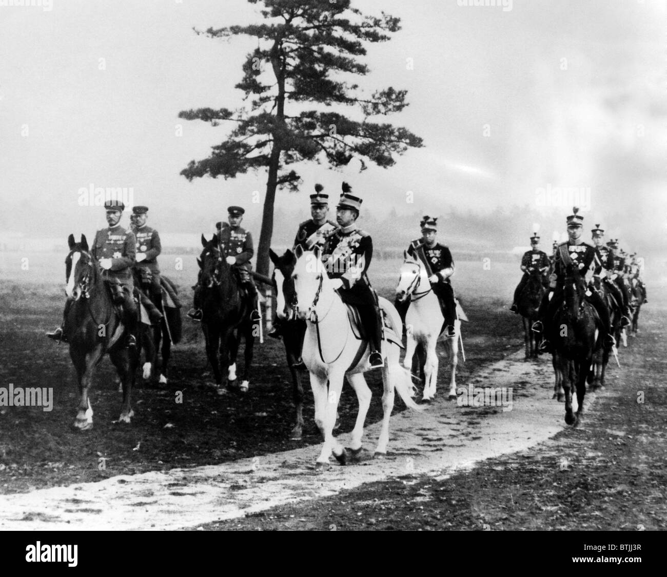 Emperor Hirohito, accompanied by members of his military suite, reviews his troops in Tokyo. ca. 1936. Courtesy: - Stock Image