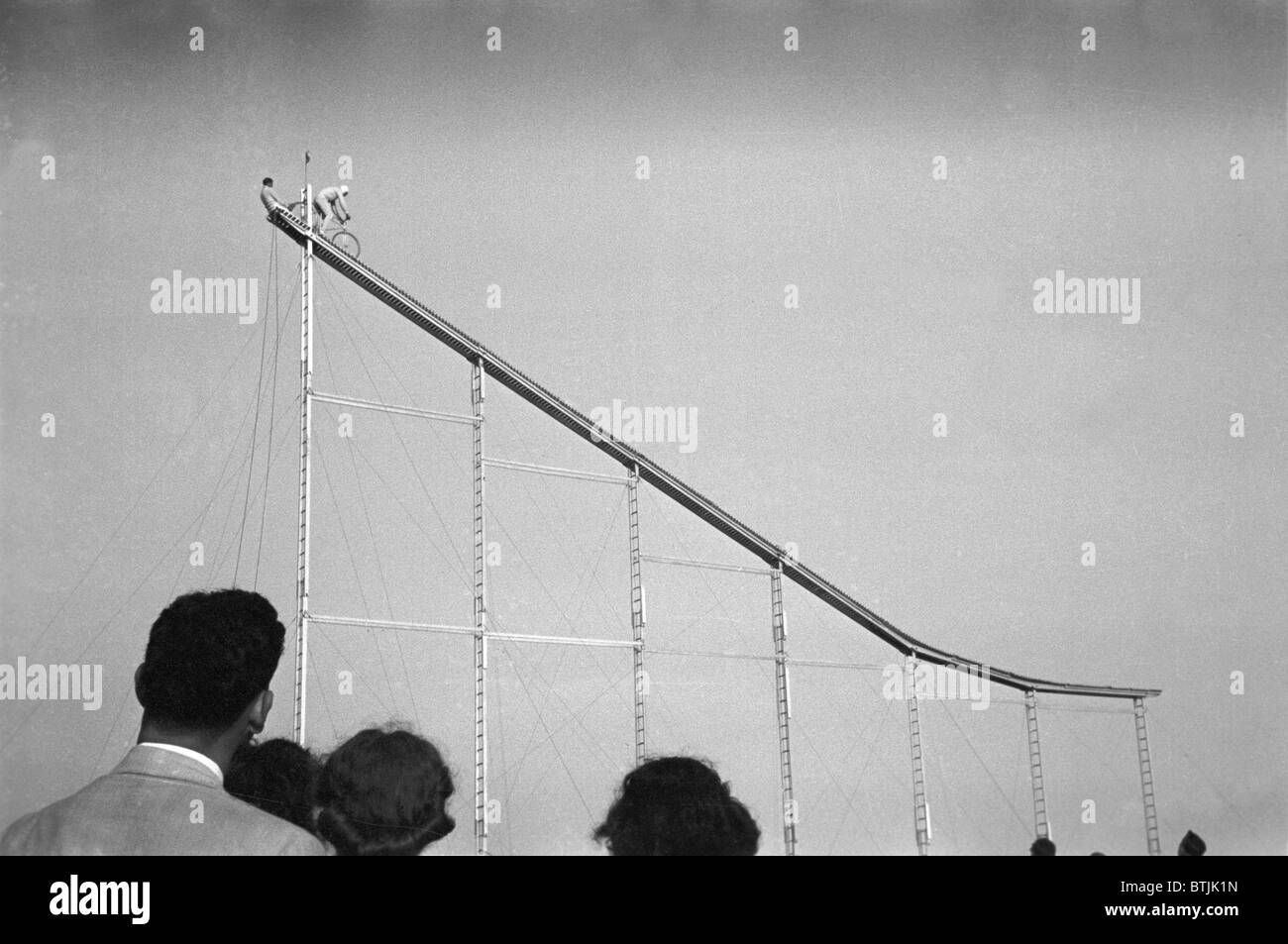 Daredevil preparing to dive into water from cycle down an elevated incline, by Lee Russell, state fair, Donaldsonville, - Stock Image