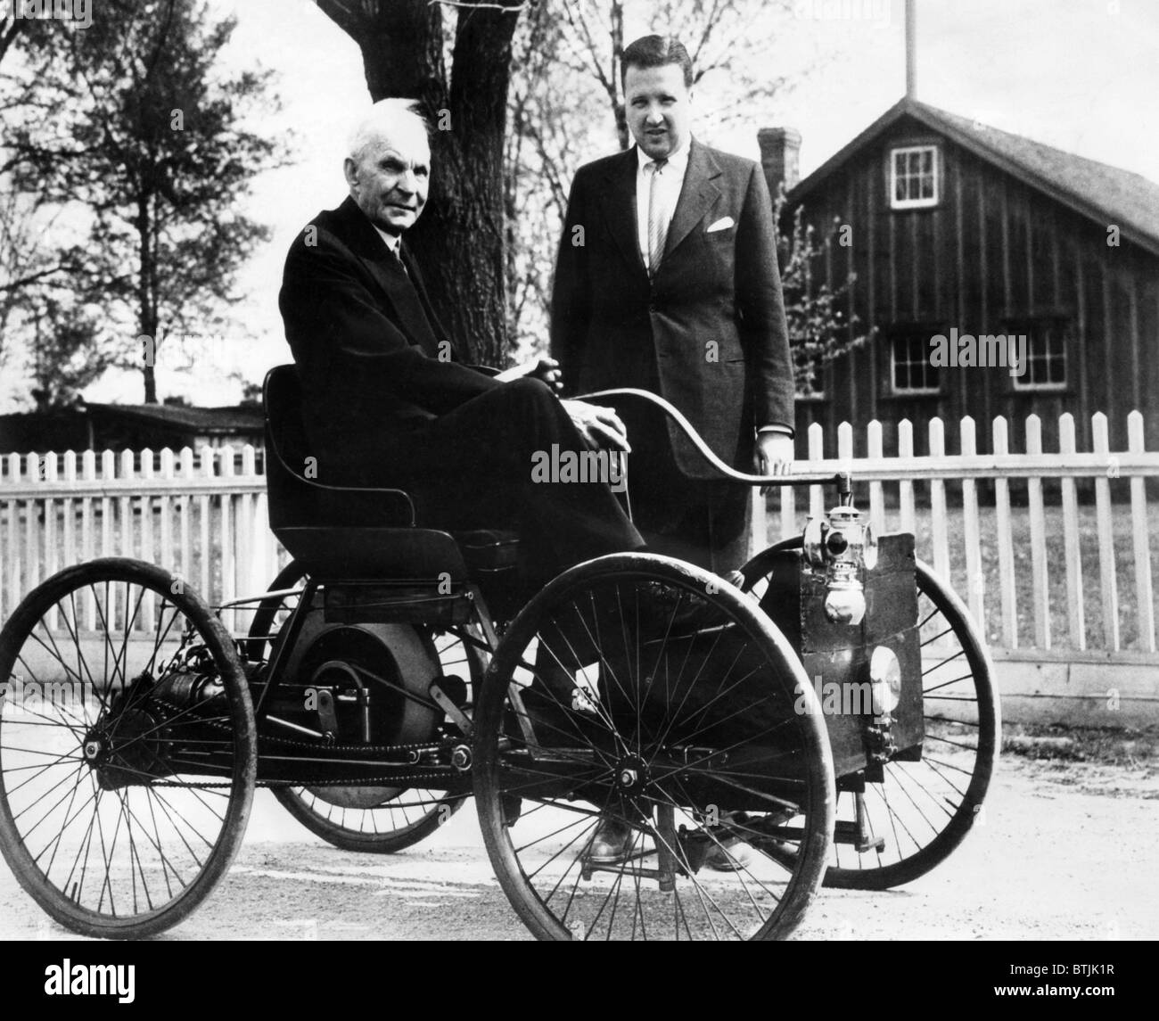 Henry Ford sits in his first Ford car built in 1896, as his grandson ...