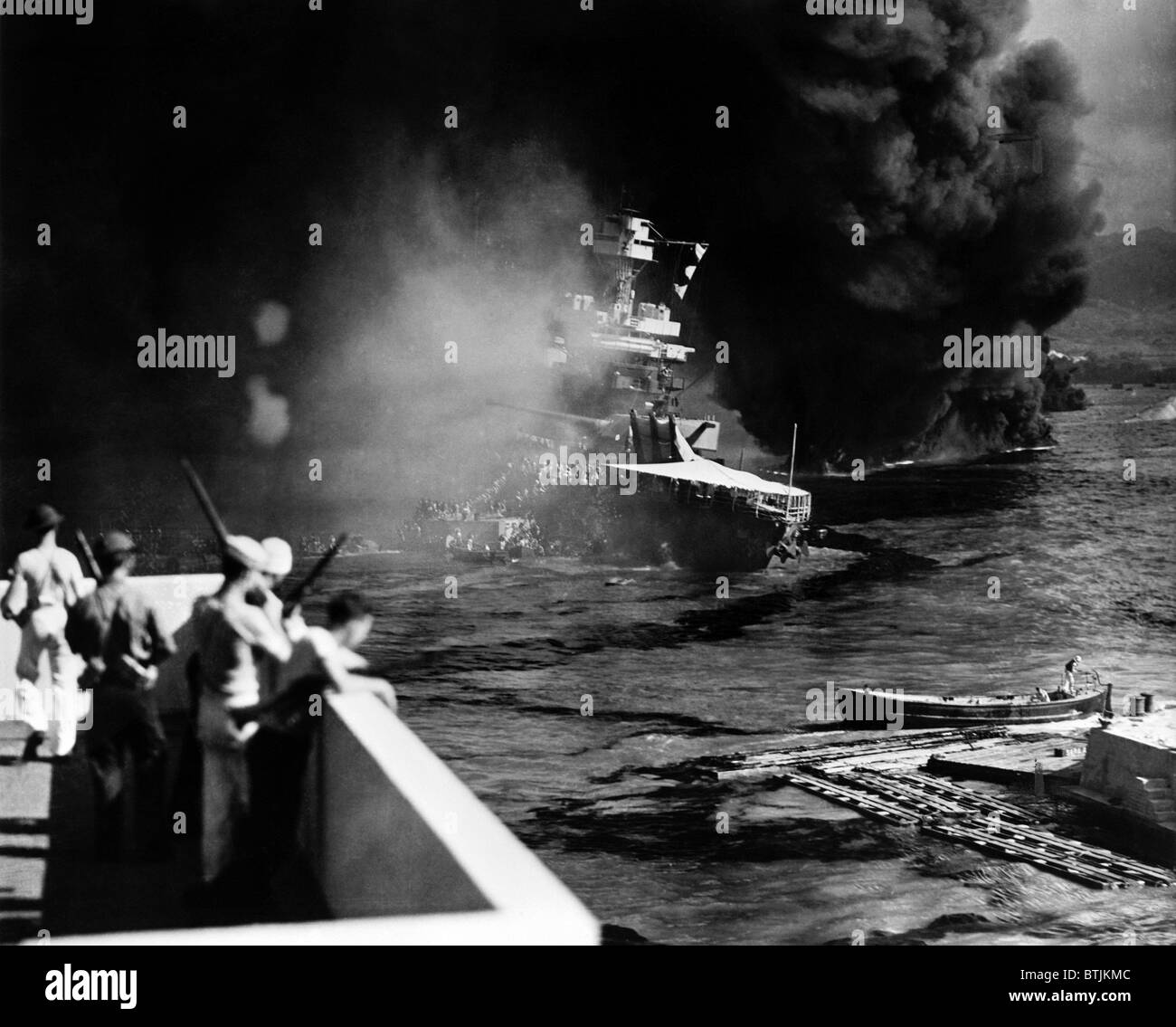 Pearl Harbor: Battered by aerial bombs and torpedoes, the U.S.S. California is evacuated as sailors and soldiers Stock Photo
