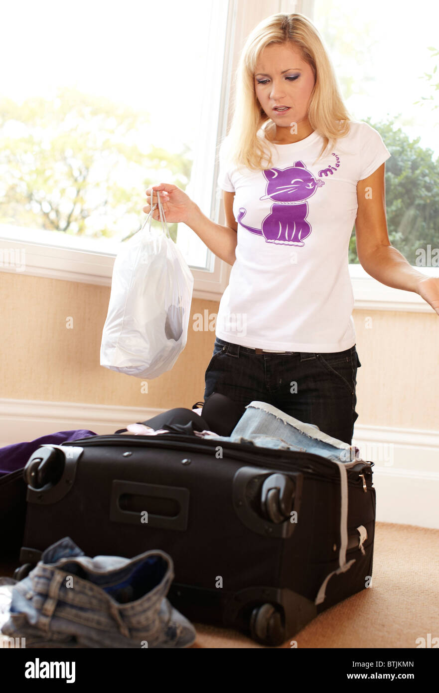 Girl packing suitcase - Stock Image