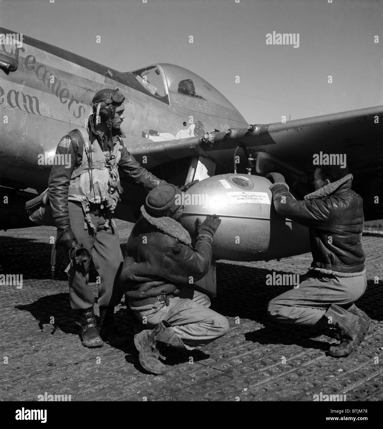 A Tuskegee fighter pilot and two airmen adjusting an external seventy-five gallon drop tank on the wing of a P-51D - Stock Image
