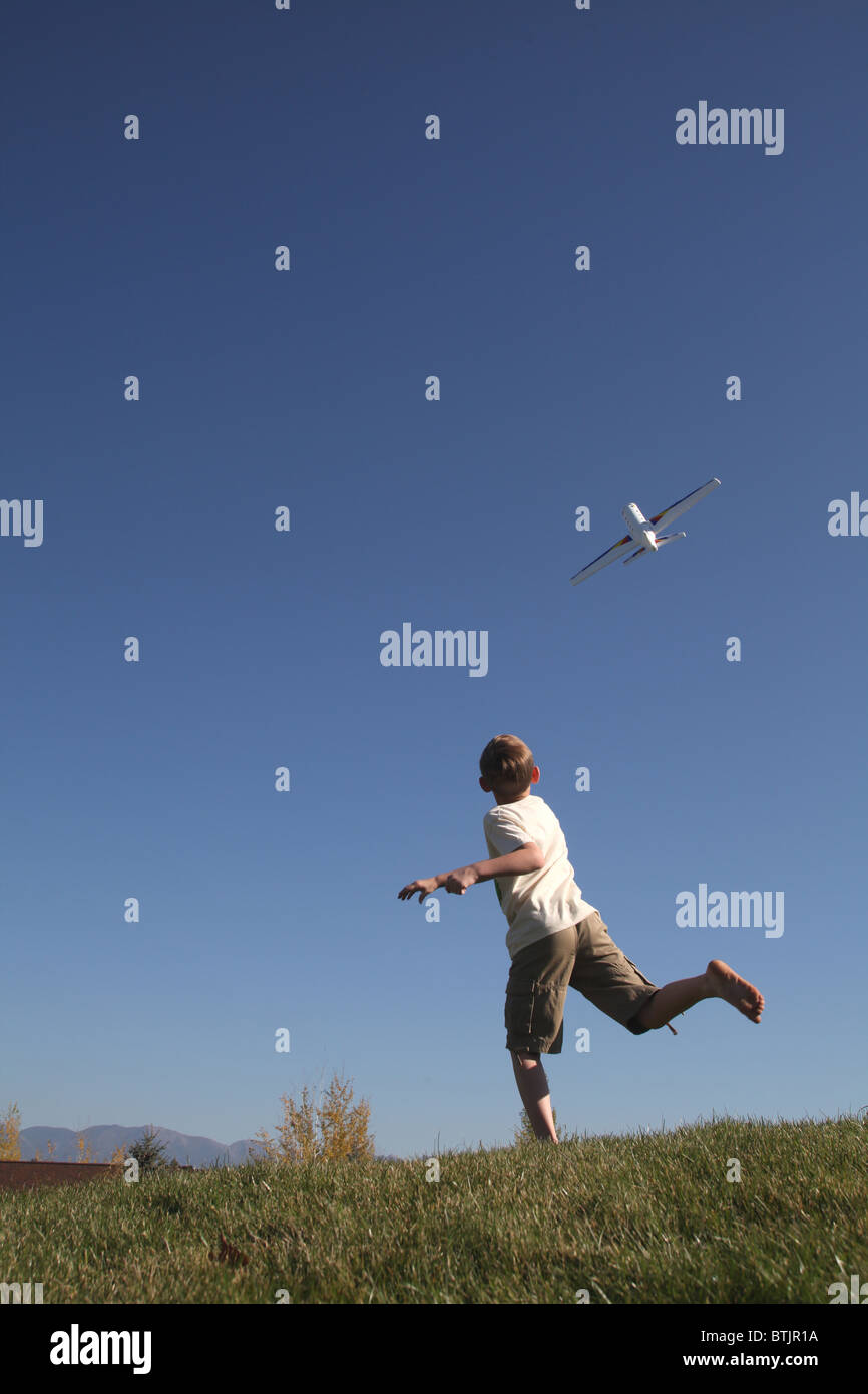 young boy throwing toy airplane into the sky - Stock Image