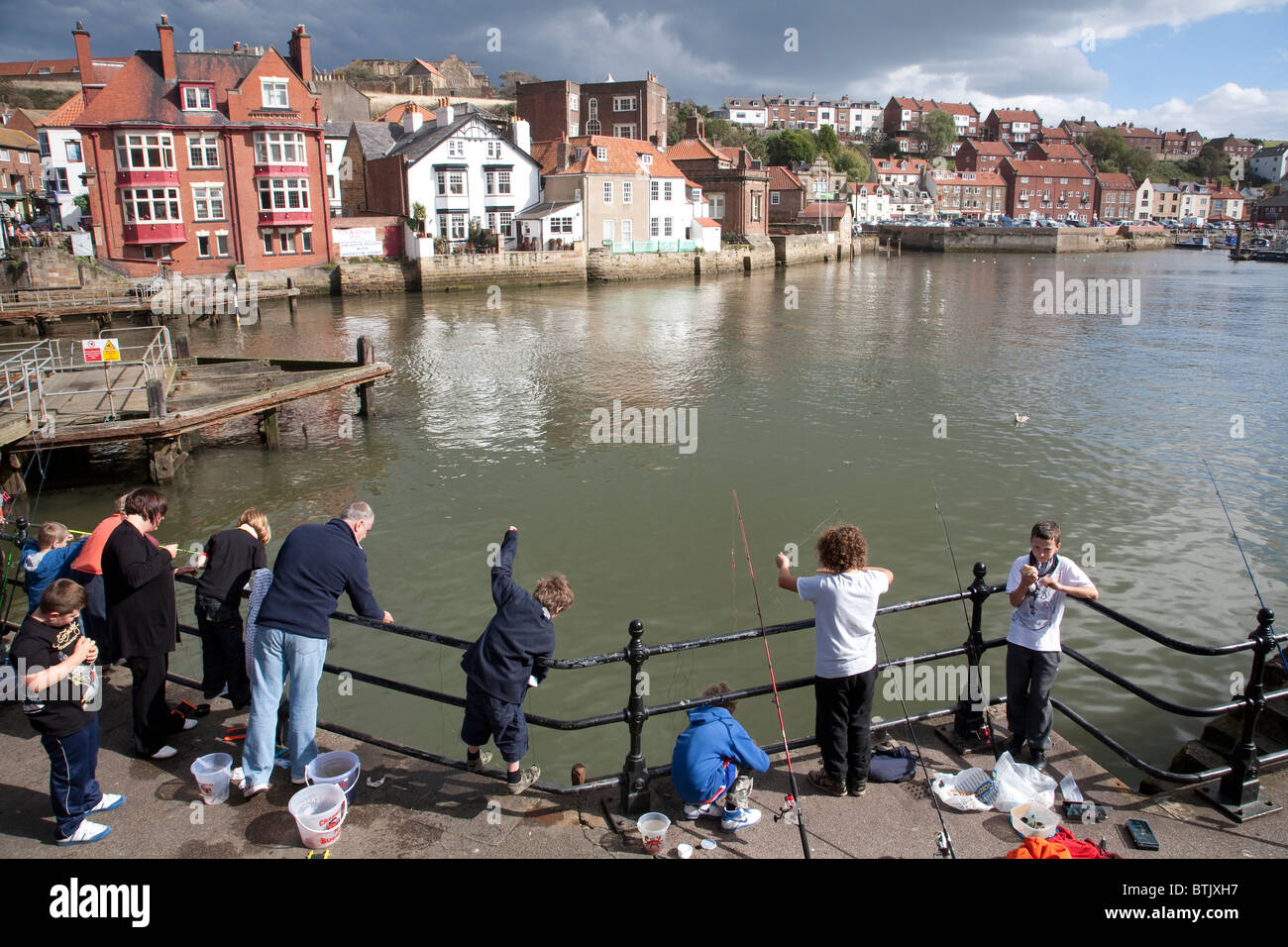 Families fishing at the mouth of the River Esk, Whitby, North Yorkshire. Photo:Jeff Gilbert - Stock Image