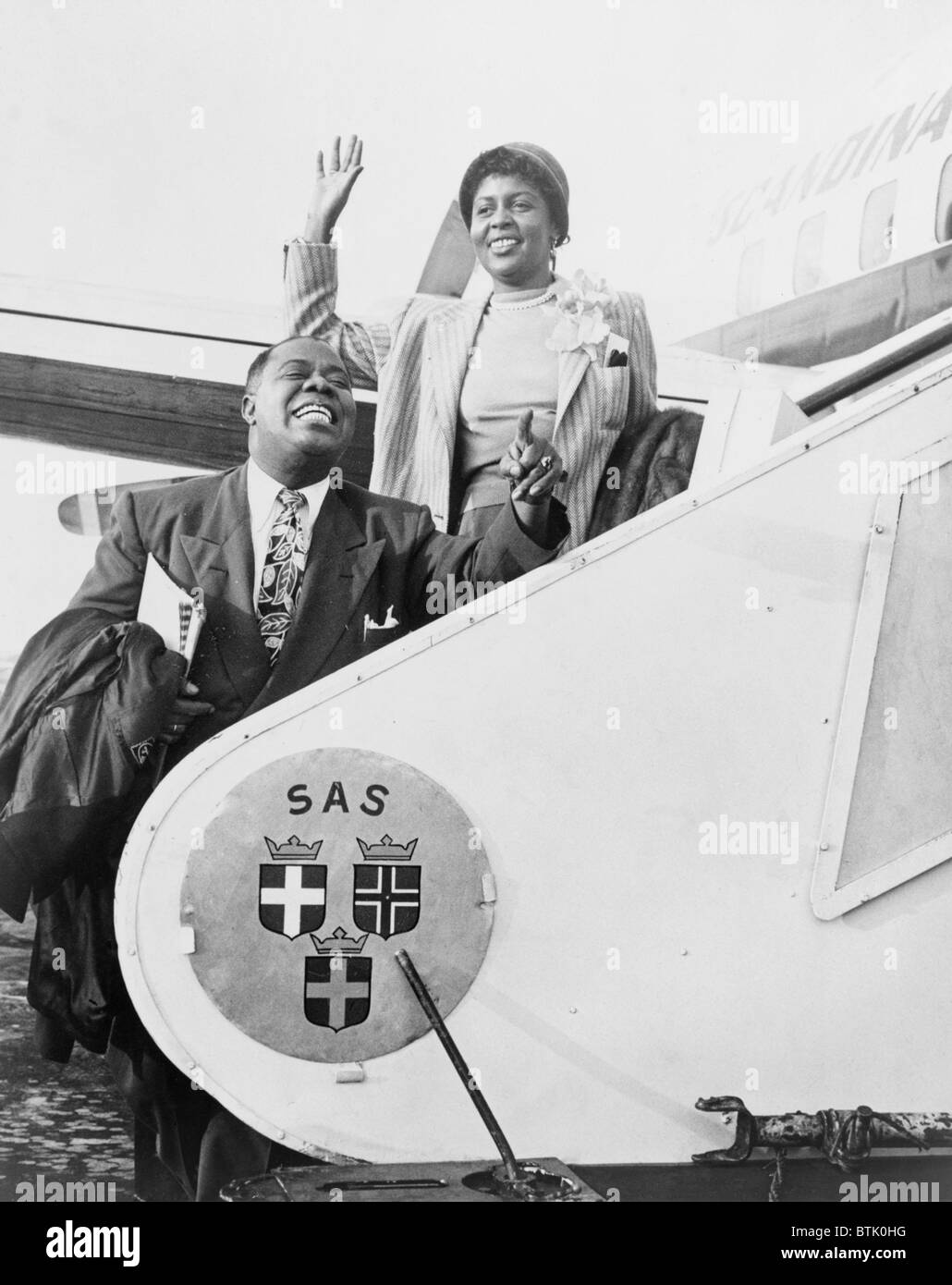 Louis Armstrong (1901-1971), African American Jazz musician, and his wife Lucille boarding airplane for Stockholm. Stock Photo