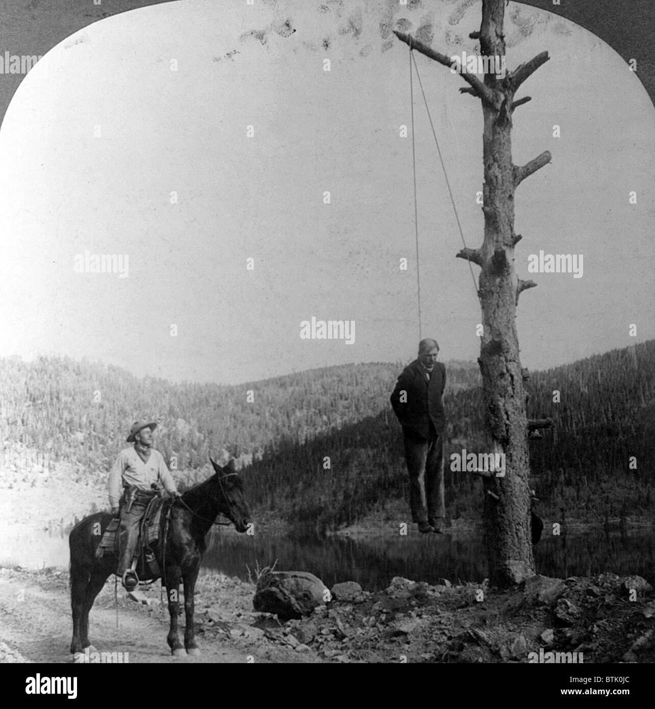 Wild West. Sheriff on horseback looking at stage coach robber hanging by neck from tree, 1911. - Stock Image