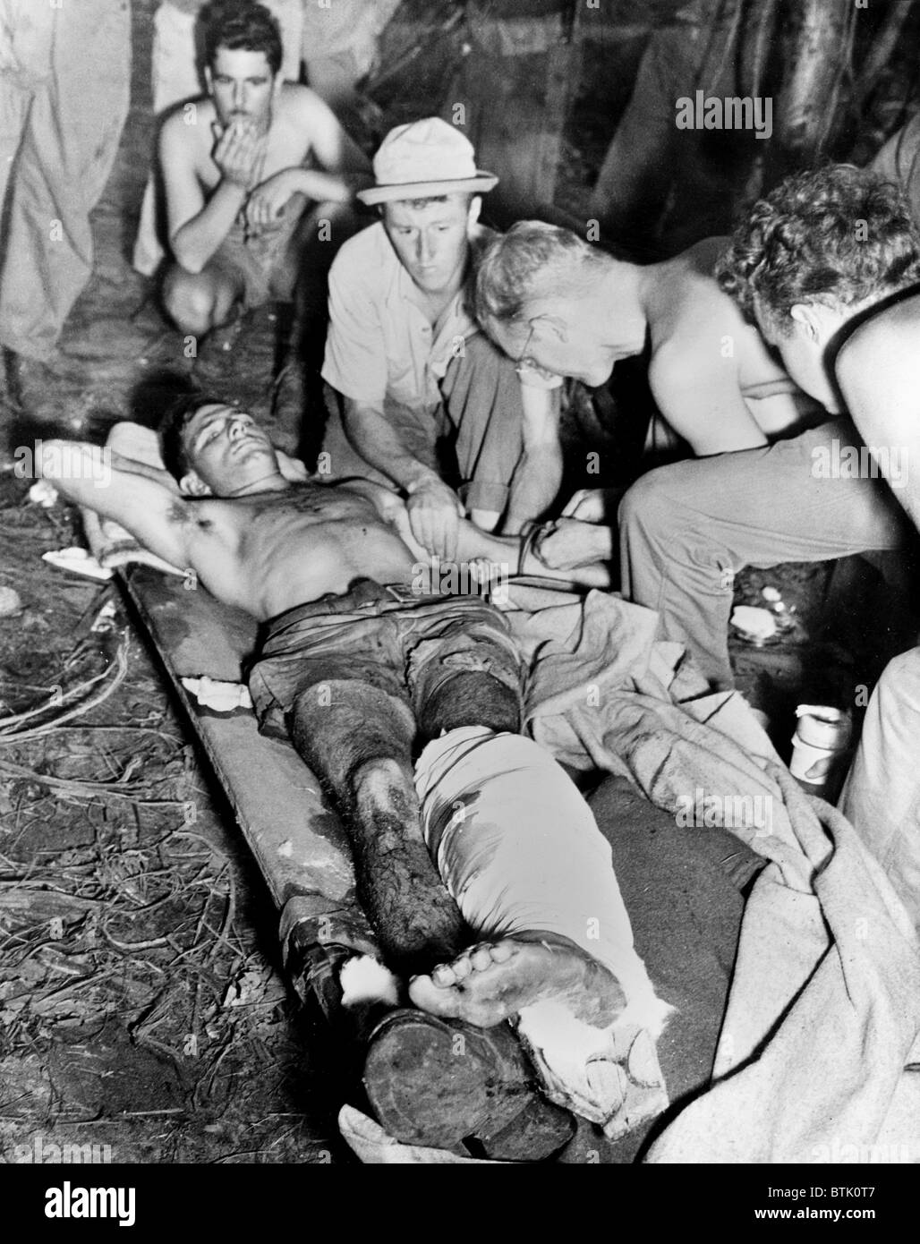 Blood Transfusion. A wounded American soldier gets a blood transfusion while assistants hover about the improvised - Stock Image