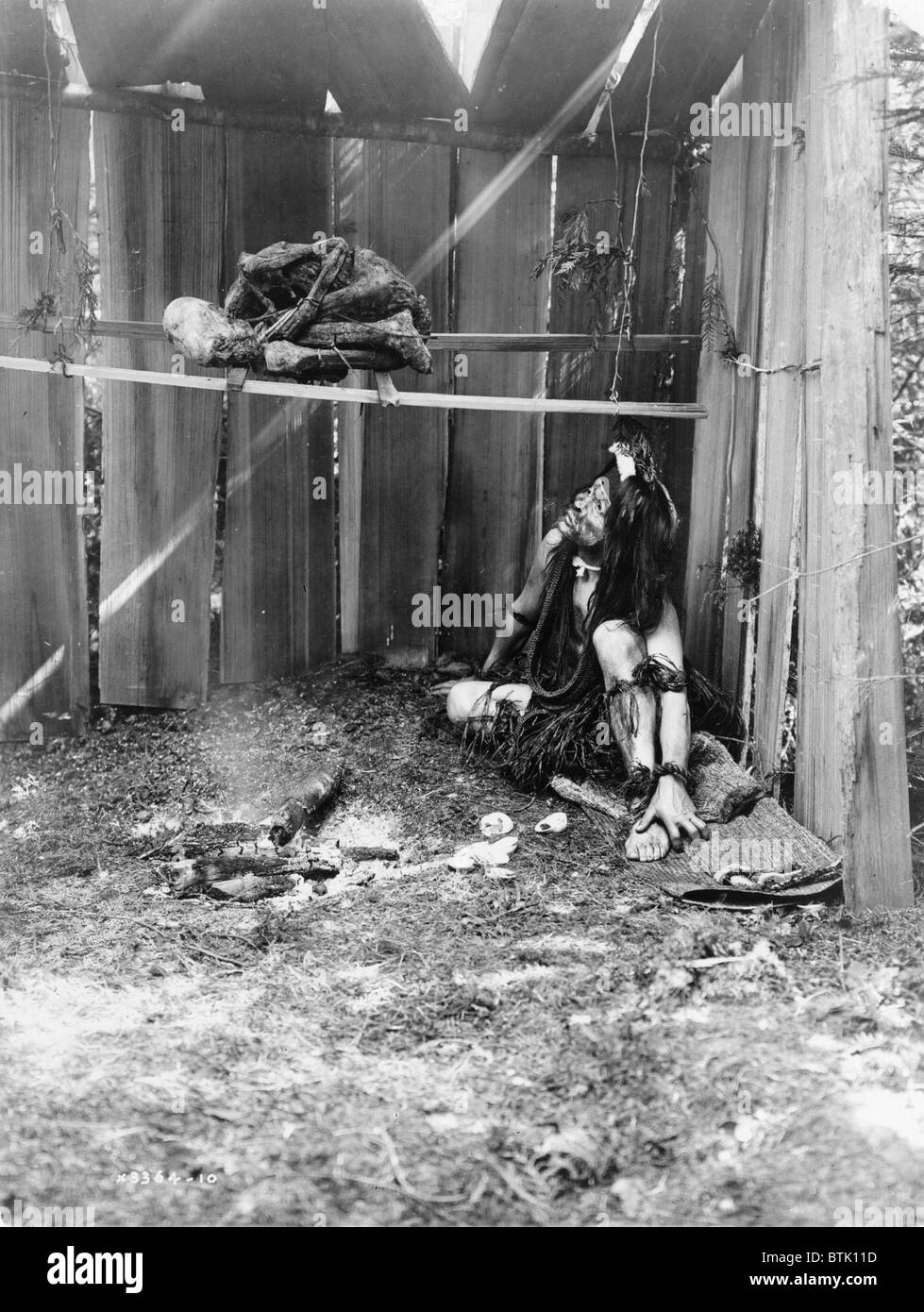 The drying mummy, Kwakiutl man inside board structure, curing mummy over smoke and coals of fire, photograph by - Stock Image