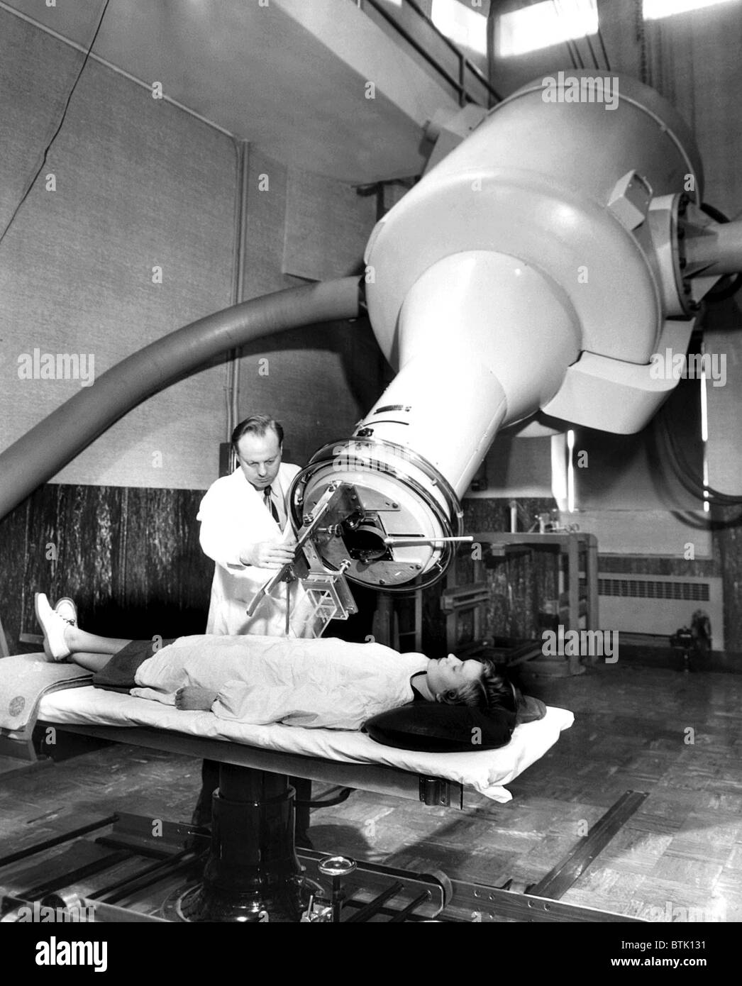 Simulating the treatment of a cancer patient, a doctor adjusts the X-ray machine at Frances Delafield Memorial Hospital, - Stock Image