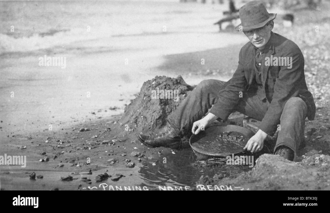 Man panning gold on Nome, Alaska beach in the early 20th century. - Stock Image