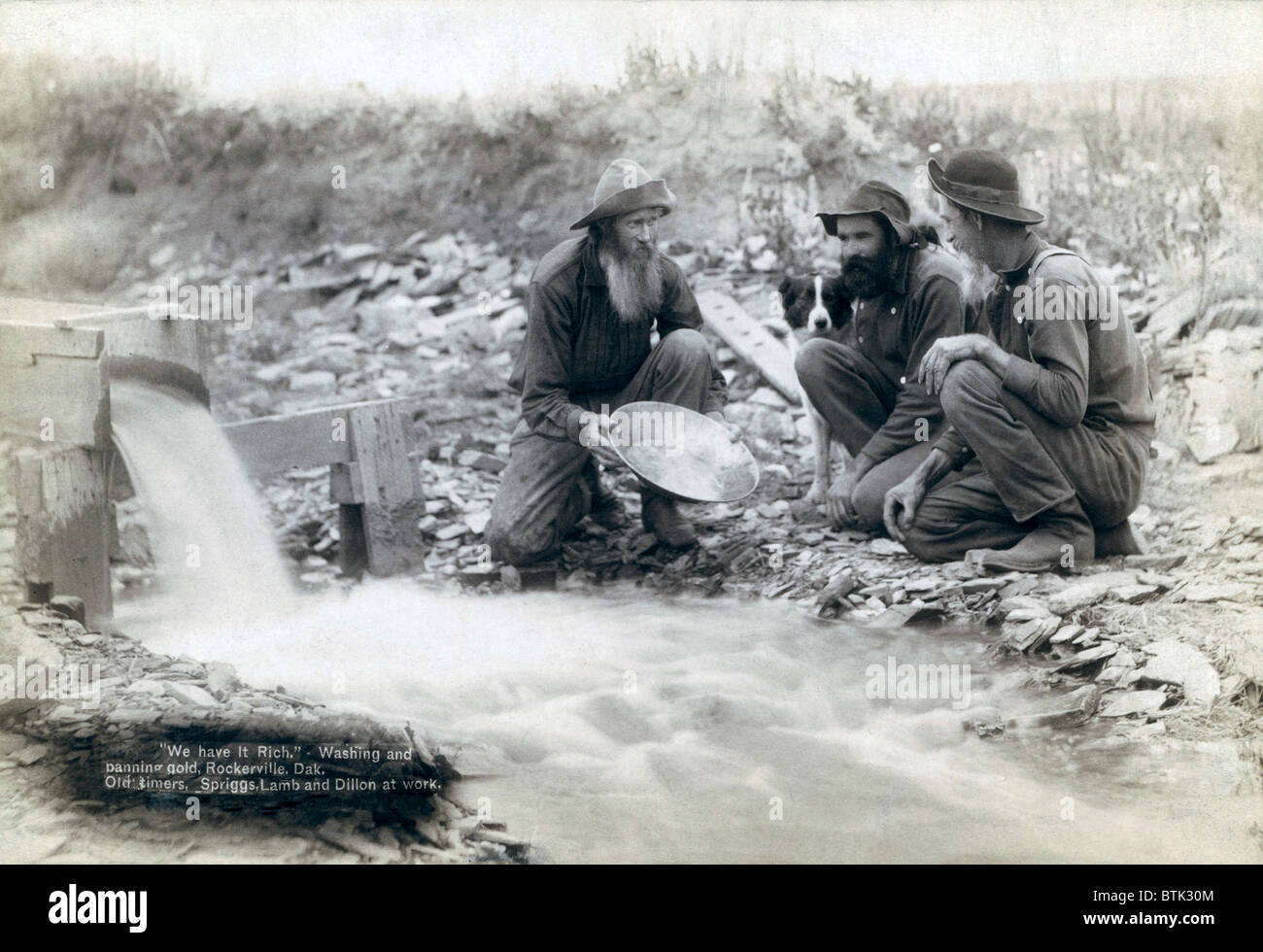 Three men, with dog, panning for gold in a stream in the Black Hills of South Dakota in 1889. Old timers, Spriggs, - Stock Image
