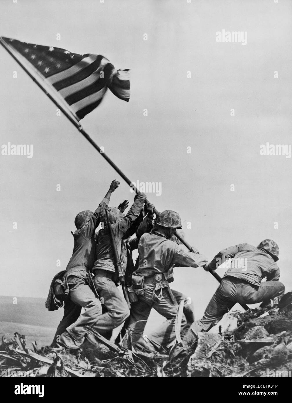 American Marines raising US flag on Mount Suribachi, Iwo Jima, Feb. 23, 1945. This is the second flag raising, using a larger flag visible to marines still ...