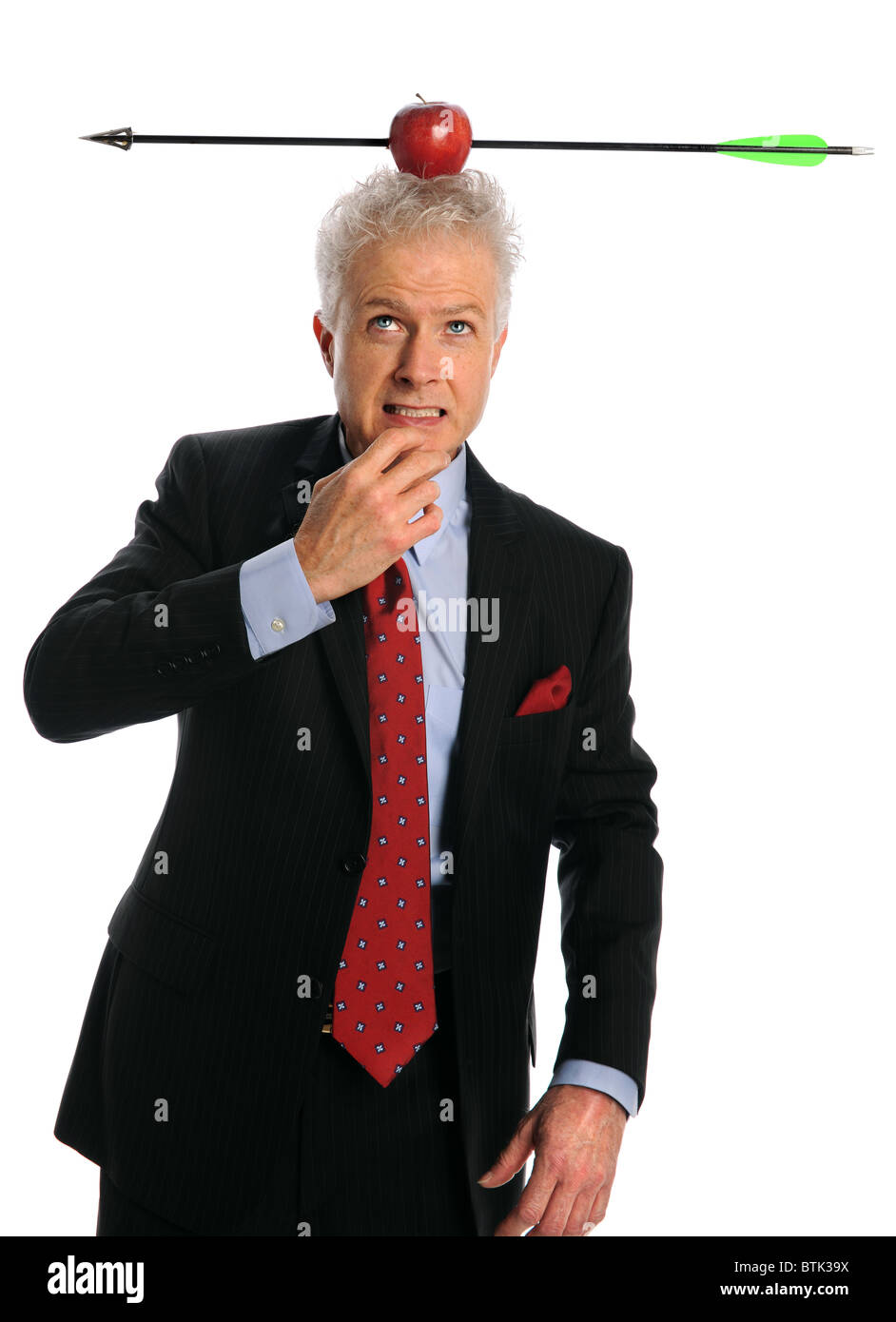 Businessman with apple and arrow on top of head isolated over white background - Stock Image