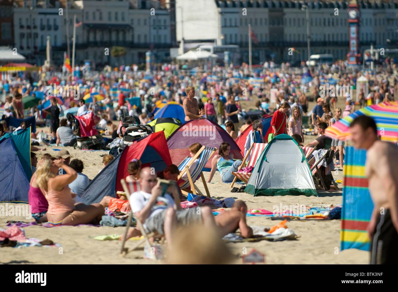 sunseeker tourists on Weymouth Beach UK - Stock Image