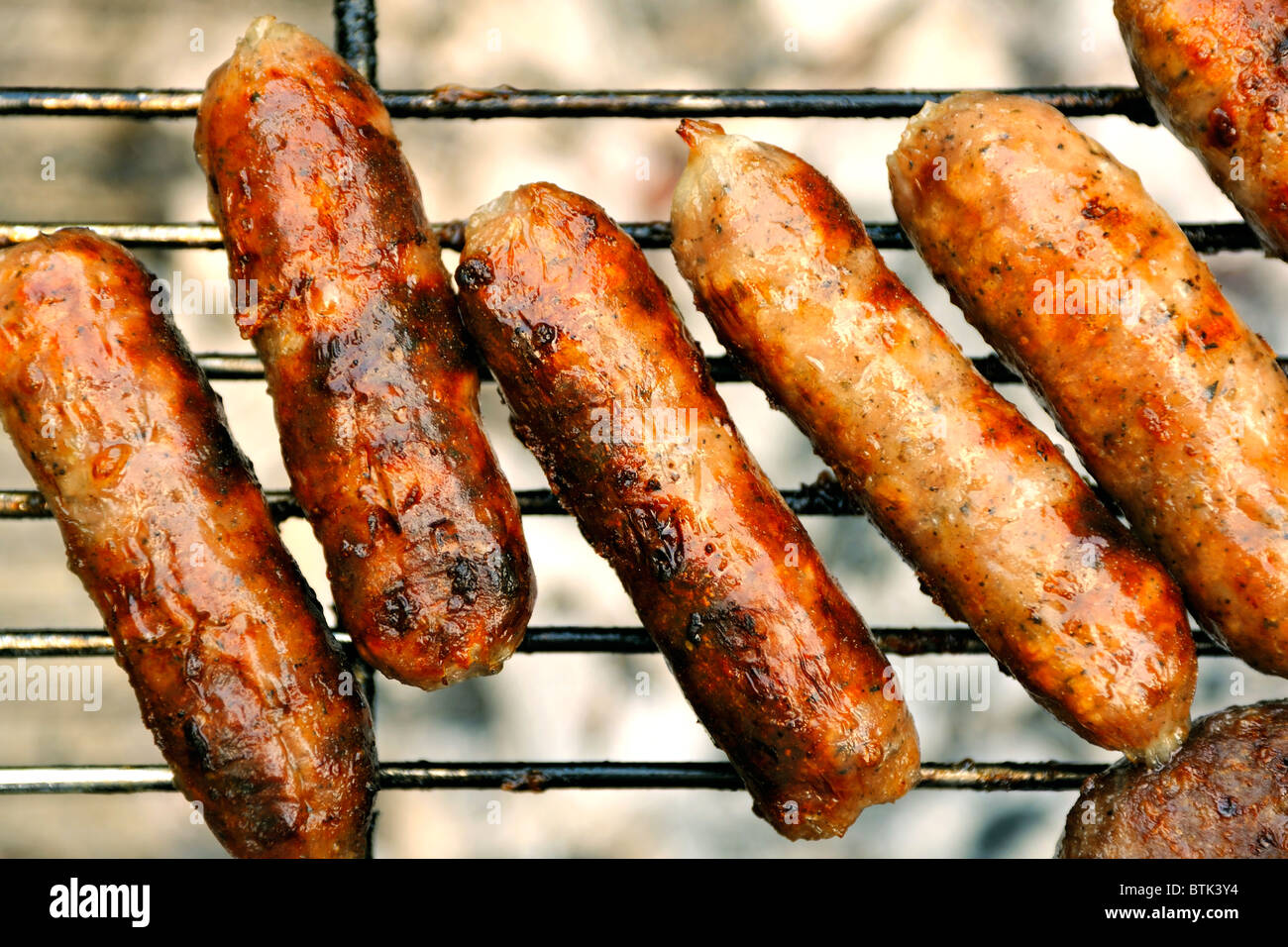 SAUSAGES ON A  BBQ - Stock Image